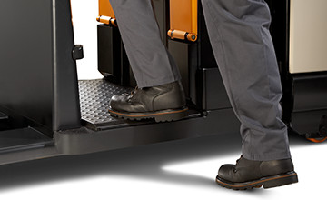 operator stepping onto the PC series pallet truck with operator-sensing floorboard