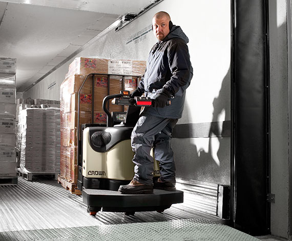 Operator unloads a truck using a Crown PE series end rider pallet truck