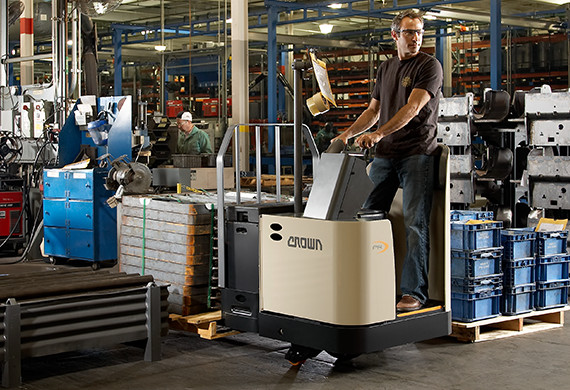 Operator moves a heavy load in a manufacturing setting using Crown PR series stand-up rider pallet truck