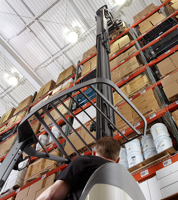 Operator traveling on an RM/RMD Series stand-up reach lift truck