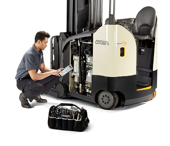 service technician performs maintenance on a crown reach truck
