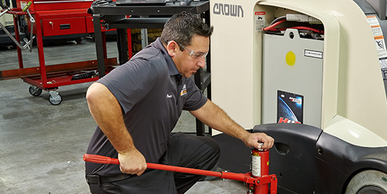 Crown service technician performs maintenance on forklift