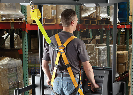 Forklift operator wearing safety harness.